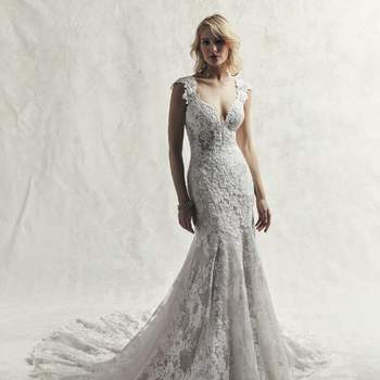 An ultra-romantic lace wedding gown, this soft fit-and-flare features shimmering motifs atop textured tulle.