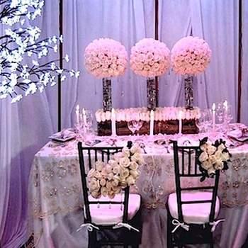 Centro de mesas con rosas rosado claro, jarros altos, bases bajas, mantel con pedrería, velas, rosas blancas para las sillas.