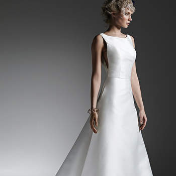 Luxe Reena Mikado creates this dramatic, structured A-line wedding dress with sophisticated bateau neckline, scene-stealing sheer panel inset at side seams, hidden pockets, and stunning open back. Finished with covered buttons over zipper closure. <img height='0' width='0' alt='' src='http://ads.zankyou.com/mn8v' />