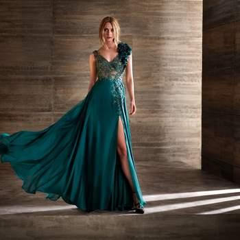 Vestido de fiesta color verde esmeralda con pequeñas aplicaciones de pedrería y abertura frontal en la falda.