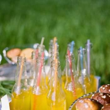 Bebidas con botellas de cristal y pajitas de colores.