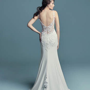 "<a href=""https://www.maggiesottero.com/maggie-sottero/alaina/11453"">Maggie Sottero</a>  Embroidered lace motifs accented in pearls and Swarovski crystals cascade over the sheer bodice of this romantic Aldora Crepe wedding dress, completing the straps, V-neckline, and illusion scoop back. Sheath skirt features an illusion cutout train accented in lace motifs and an attached beaded belt with Swarovski crystals. Finished with pearl buttons and zipper closure."