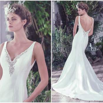 "Structured Elodie mikado wedding dress with stylized seams dramatically flares to create a refined fit and flare silhouette. The deep V-neckline and open back are embellished with crystals and beads for added luxury and dimension. Finished with crystal buttons over zipper closure.   <a href=""https://www.maggiesottero.com/maggie-sottero/roan/9750"" target=""_blank"">Maggie Sottero</a>"