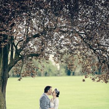 Los novios besándose en un precioso parque.