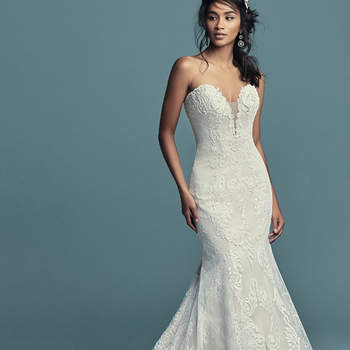 "<a href=""https://www.maggiesottero.com/maggie-sottero/freida/11474"">Maggie Sottero</a>  This soft yet alluring fit-and-flare features alternating sections of allover lace along the sides and cascades of lace motifs and crosshatching down the middle. An illusion plunging neckline completes the elegance of this strapless tulle wedding dress. Finished with inner corset and covered buttons over zipper closure."