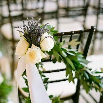 Lavande, roses blanches et branchages : une association parfaite pour la décoration des chaises. Crédit photo : Lisa Lefkowitz Photography