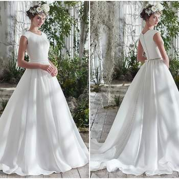 "Rich Shavon organza adds an exquisite dose of romantic elegance to this voluminous A-line wedding dress, detailed with covered buttons trailing from neck to hemline. Finished with cap-sleeves, soft scoop pleated neckline, hidden pockets, and covered buttons over zipper closure. Detachable beaded belt sold separately.   <a href=""https://www.maggiesottero.com/maggie-sottero/anita-marie/9768"" target=""_blank"">Maggie Sottero</a>"