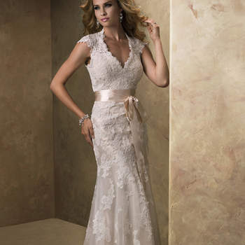 "A dreamy lace and tulle slim line gown with V-neckline and cap-sleeves features a separate slip gown of Vogue Satin to be worn below. The alluring open back is finished with a covered button over zipper closure. Includes a detachable satin ribbon belt. <a href=""http://www.maggiesottero.com/dress.aspx?style=12623"" target=""_blank"">Maggie Sottero</a>"