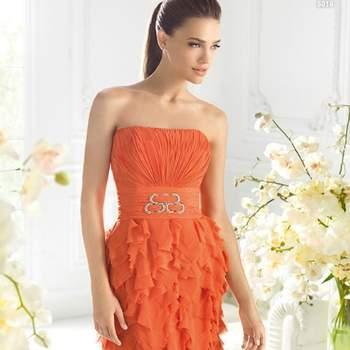 Abito color arancione senza spalline con fascia in vita abbellita da spilla gioiello e gonna multistrato con veli di organza