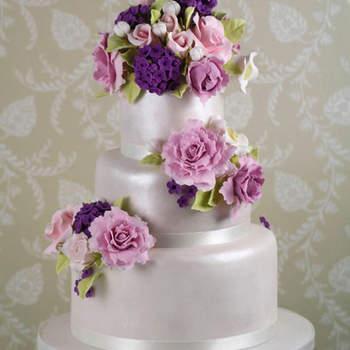 Tarta cubierta con fondant perlado blanco y bouquets de lilas rosas y peonías realizadas a mano en azúcar.