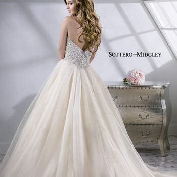 Decadent crystal bodice complete with demure illusion center neckline and romantic Chic Organza skirt. Finished with zipper over inner corset and crystal button closure. Includes detachable center front motif.