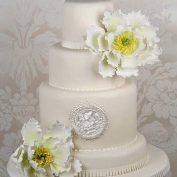 Una tarta moderna y sofisticada color marfil con grandes peonías de azúcar y roseta pintada con colorante perlado comestible.