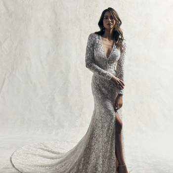 This gorgeous sleeved wedding gown is comprised of allover lace motifs atop tulle in a sheath silhouette.