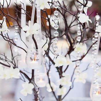 Très jolis centres  de table arbres blancs & argentés décorés de guirlande de cristal. Source : mariage-idees