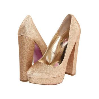 Chaussure en or rose avec des talons hauts et le plate forme plus carré. Photo : Paris Hilton