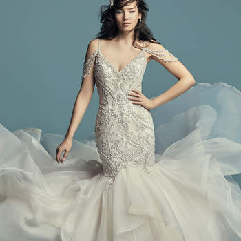 "<a href=""https://www.maggiesottero.com/maggie-sottero/brinkley/11427"">Maggie Sottero</a>  Glamorous and vintage-inspired, this mermaid wedding dress features a tulle bodice accented in beaded embroidery and Swarovski crystals. Beaded illusion cold-shoulder sleeves complete the sweetheart neckline and plunging V-back, also trimmed in beading and illusion. Fit-and-flare skirt comprised of tiered Chic Organza trimmed in horsehair. Finished with crystal buttons over zipper closure."