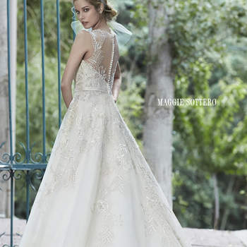 "This tulle ballgown is the epitome of bridal bliss. Complete with dazzling Swarovski crystals accenting the bodice and illusion neckline, scalloped lace hemline, and delicate satin belt at the waist. Finished with pearl button over zipper and inner elastic closure.  <a href=""http://www.maggiesottero.com/dress.aspx?style=5MS021"" target=""_blank"">Maggie Sottero Spring 2015</a>"