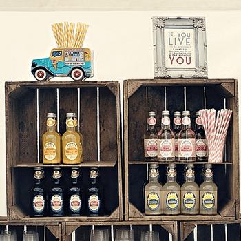 Detalle de las bebidas de sabores y su presentación en cajas de madera antigua.