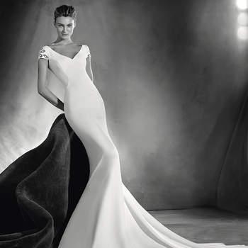 Elegantíssimo vestido de noiva estilo sereia com um espetacular decote à frente em bico e amplo decote nas costas adornado com finos botões. Um modelo que embeleza as curvas femininas e que apresenta detalhes de pedraria nas mangas que lhe conferem um toque chique.