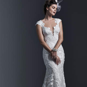 Dramatic laser cut lace appliqués lay atop tulle in this form-fitting sheath wedding dress; with demure illusion back. Finished with plunging neckline and covered buttons over zipper closure. <img height='0' width='0' alt='' src='http://ads.zankyou.com/mn8v' />
