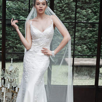 "An unexpected plunging neckline adds an extra dose of glamour to this otherwise demure lace sheath wedding dress. Lace appliqués scattered along a tulle bodice create a slinky, sensational silhouette. Finished with dainty spaghetti straps and covered buttons over zipper closure.  <a href=""http://www.maggiesottero.com/dress.aspx?style=5MN672"" target=""_blank"">Maggie Sottero</a>"