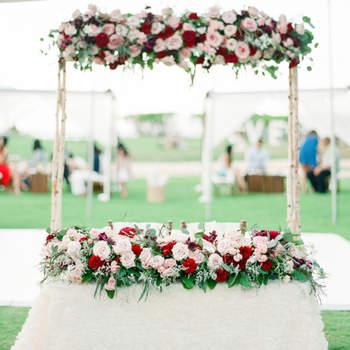 Altar con decoración floral blanca, verde y roja. Credits: Aria Studios