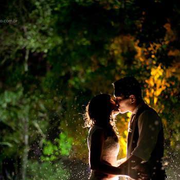 Para mim essa foto foi muito especial, pois eles se casaram na Mansão das Heras-RJ, ao ar livre, e no dia do casamento, quando faltavam 10 minutos para a entrada do cortejo, desabou uma chuva imensa e mesmo assim a noiva quis entrar. Mesmo se molhando toda! Sem derramar lágrimas, sem lamentar pela chuva. Achamos isso incrível, e rapidamente nos posicionamos debaixo de chuva com equipamento e tudo para fotografar. Os convidados ficaram todos debaixo da chuva sem questionar, todos por amor ao casal, com sorrisos de alegria e muita emoção, e o que poderia ser uma tragédia para muitos, foi felicidade para todos, e muita diversão para nós que aproveitamos a chuva para fazer a foto que pra mim foi uma das mais lindas que fiz até hoje.