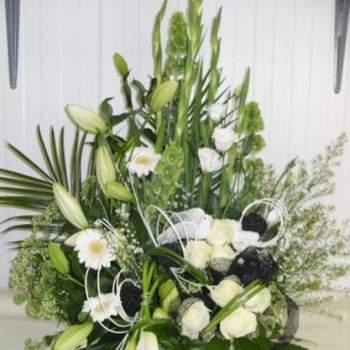 Composition florale Lune, comprenant des lys, germinis, roses, arums, asters, glaIeuls, lysianthus et molucelles le tout est présenté en hauteur et dans une verrerie - Crédit photo: Twenga