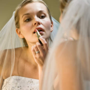 Bride applying make-up in mirror