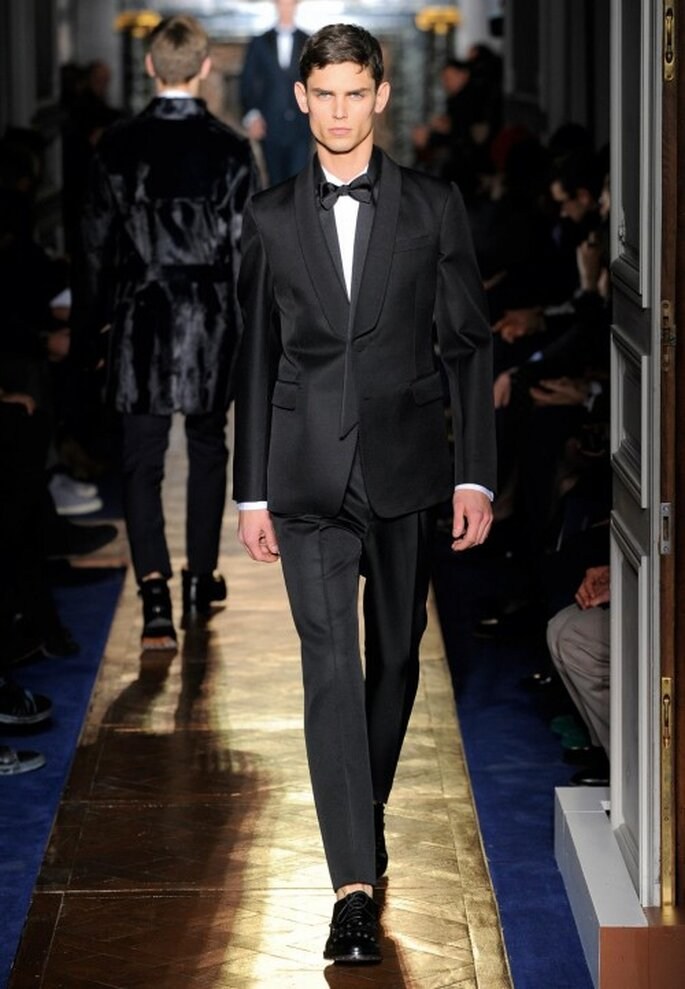 Traje de novio formal para boda en color negro con acabado lustroso y moño elegante - Foto Valentino