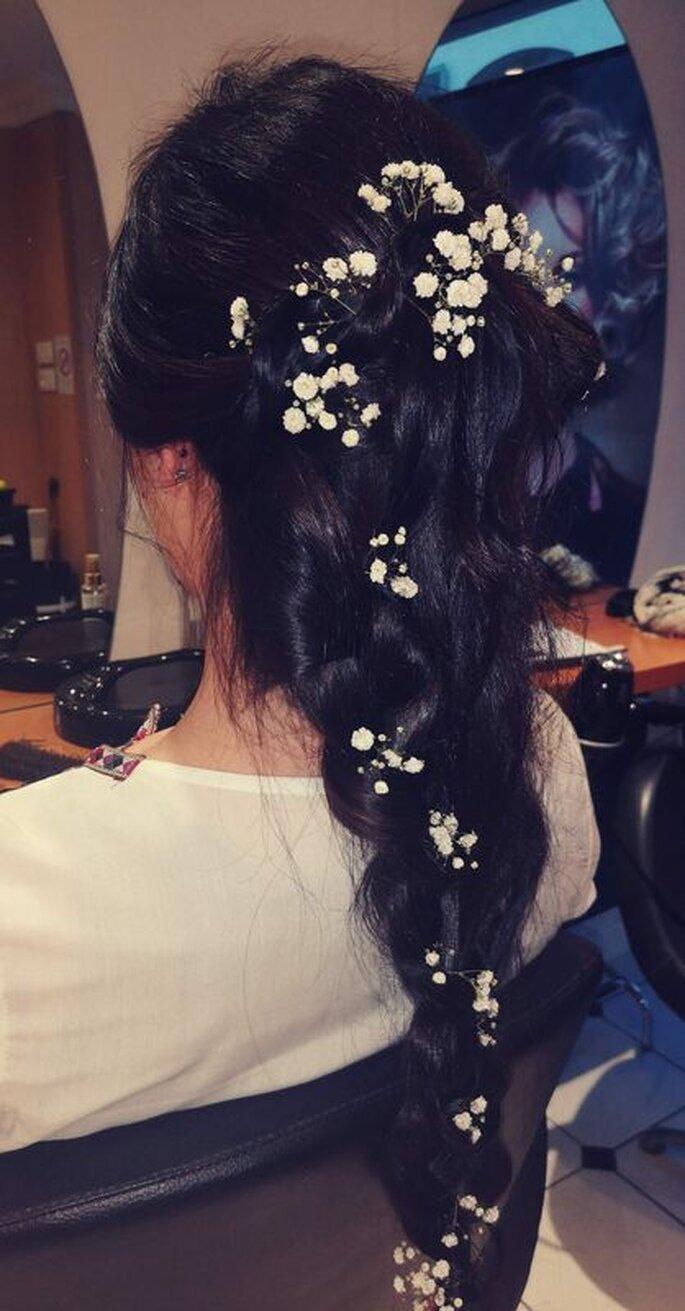 Coiffure réalisée par Morgane, sur une mariée. Il s'agit ici d'une tresse sur laquelle sont parsemées de petites fleurs blanches