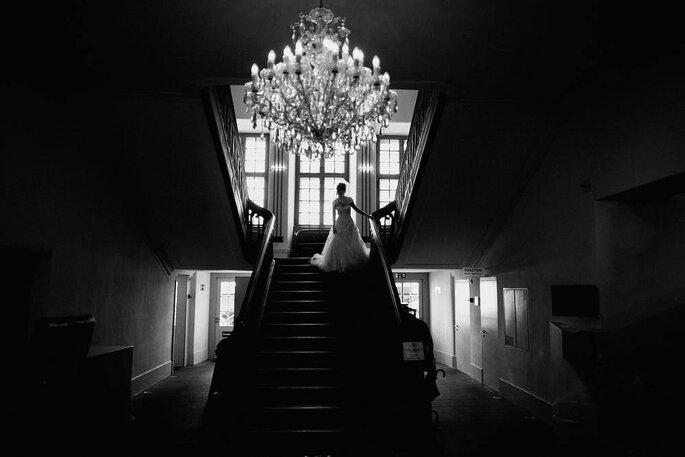 Eine Braut steht am Fuße einer Treppe. Über ihr thront ein Leuchter.