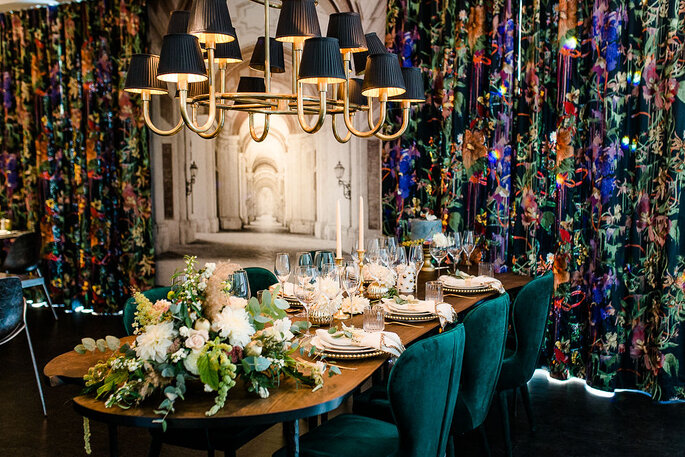 Opulente Hochzeitsdekoration in Gold- und Grüntönen an den Hochzeitstischen.