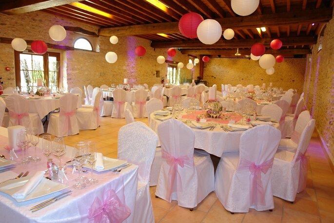 Domaine de Marolles, salle décorée avec des lampions et des tables et chaises blanches ornées de décorations roses