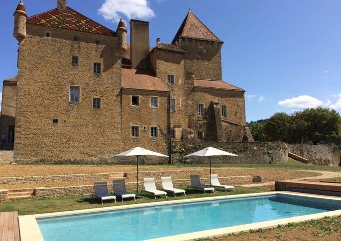 Un château historique avec une piscine en contrebas, en Bourgogne