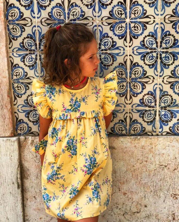 menina com vestido amarelo e flores azuis encostada parede