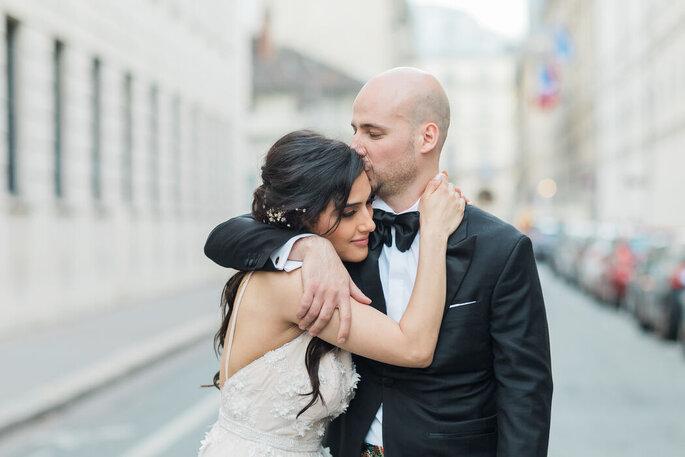 Des mariés se prenant dans les bras dans un décor urbain.