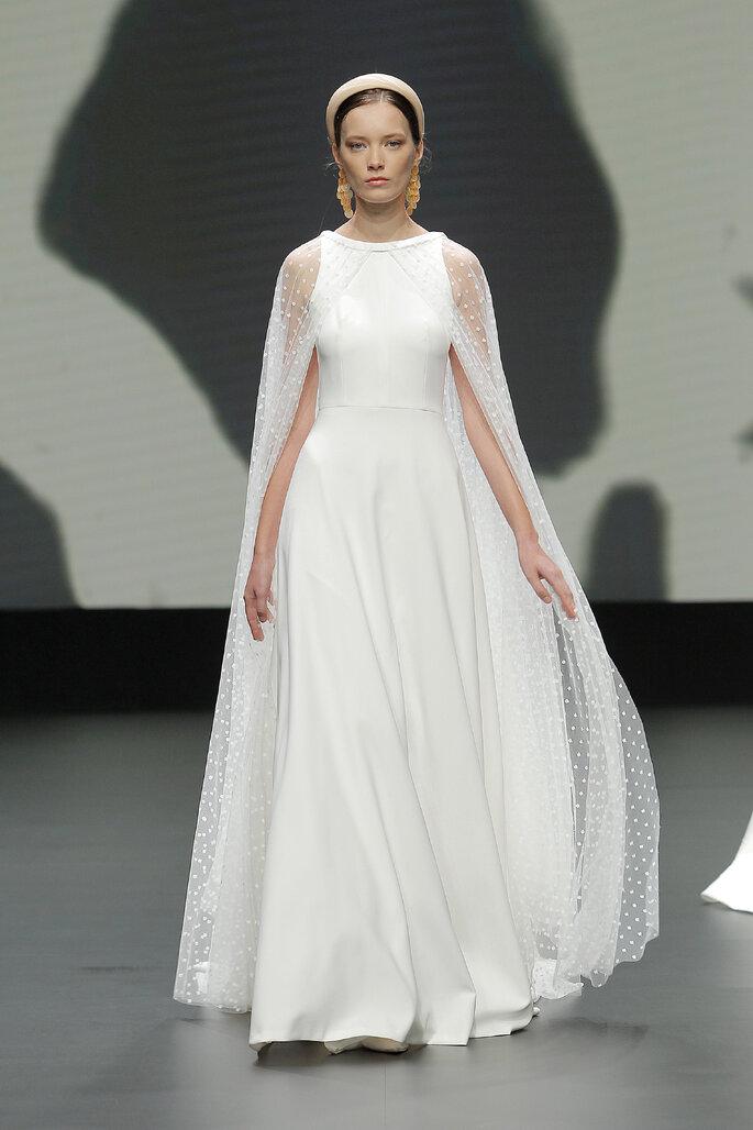 Colección Vestido de Novias 2021 Jesús Peiró vestido de novia con escote barco con capa larga de transparencia en los hombros