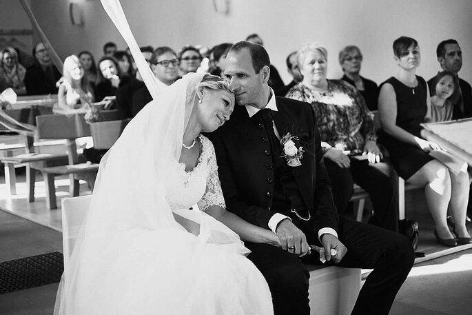 Ein Brautpaar bei der Trauung, die Braut hat ihren Kopf auf die Schulter des Bräutigams gelegt, der küsst ihren Kopf.