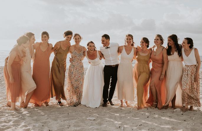 Les mariés entourés de leurs proches se retrouvent sur la plage dans un décor idyllique