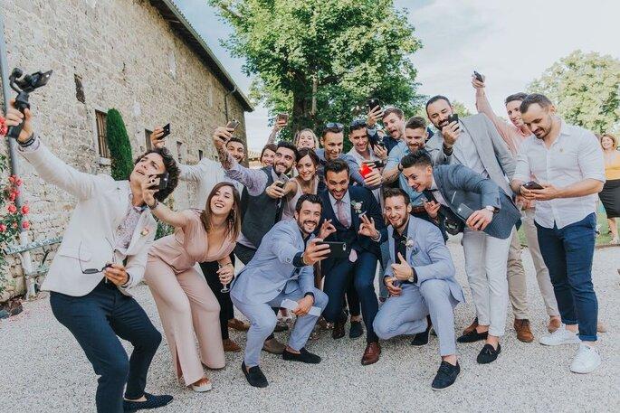 Un groupe d'invités se prend en photo lors d'un mariage - selfie - photographie posée en groupe originale
