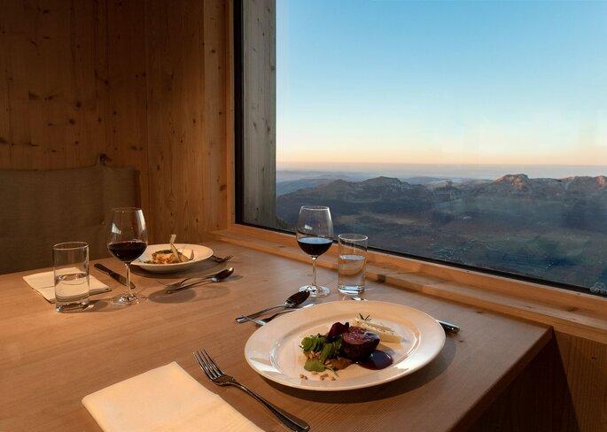 Zwei Teller stehen auf einem Tisch neben einem Fenster. Draußen ist die Alpenkette zu sehen.