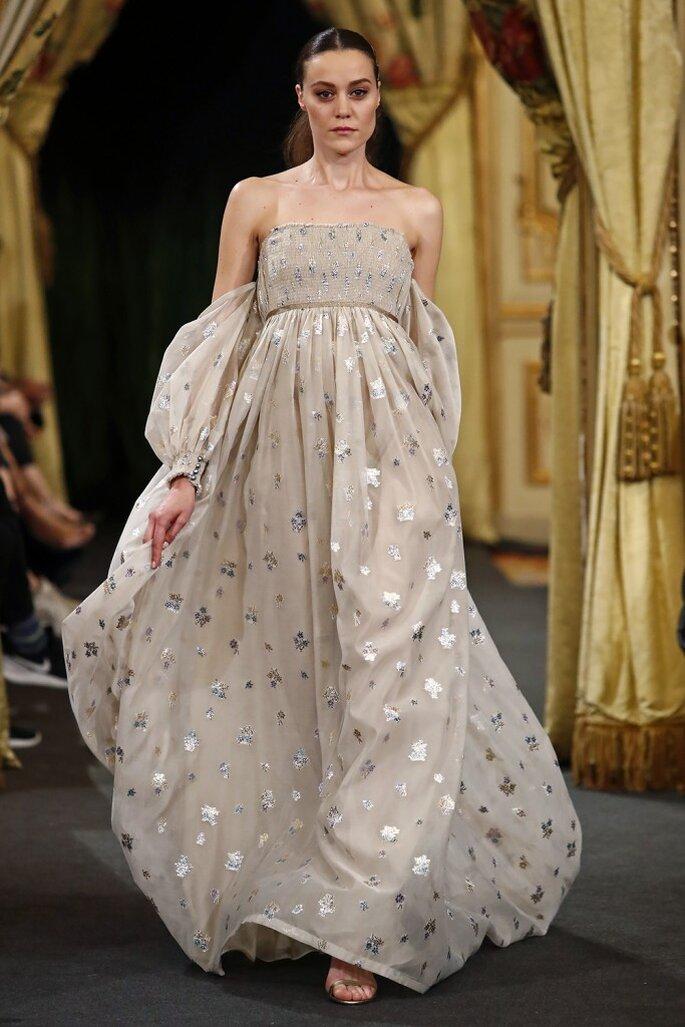 Vestido de novia corte imperio beige con estampados dorados y plateados con escote recto y mangas abombadas con caída por debajo de los hombros