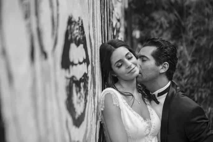 Alexandre Moulard : un marié embrasse le cou de sa femme contre un mur sur lequel est dessiné une bouche