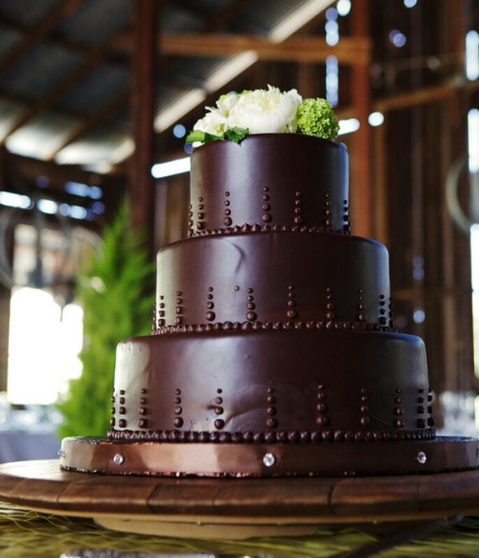 Gâteau de mariage au chocolat avec des fleurs blanches sur le dessus. Photo: Style Me Pretty