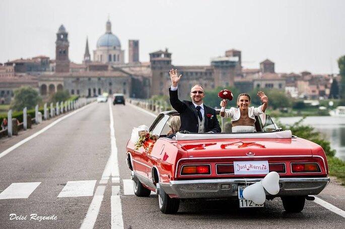 noivos se despendem de convidados em carro conversível