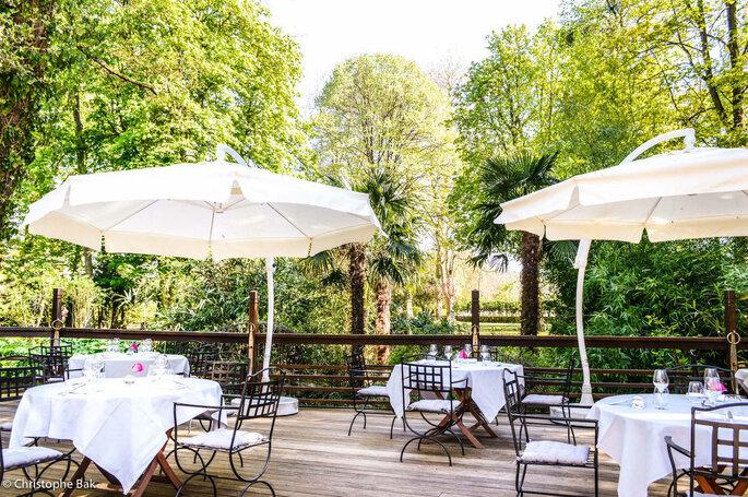 Les Jardins d'Épicure - Terrasse en amont du parc arboré, avec des tables dressées pour un dîner