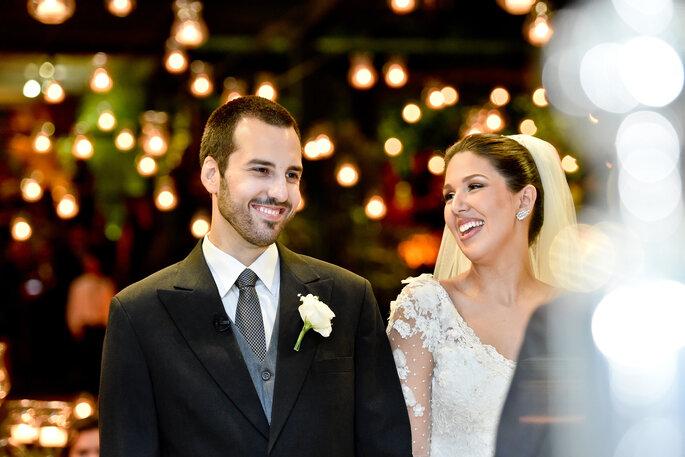 noivos no altar recebendo bençãos de celebrante