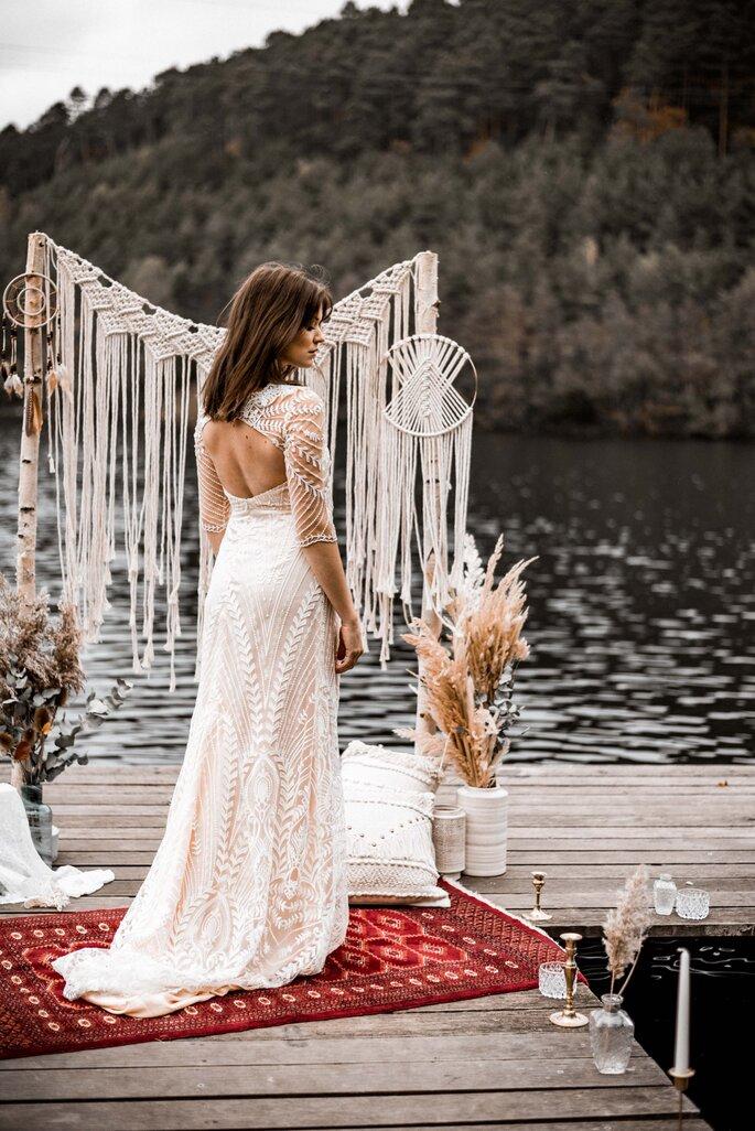 Eine Braut auf einem Bootssteg. Sie trägt ein bodenlanges Brautkleid mit tiefem Rückenausschnitt.