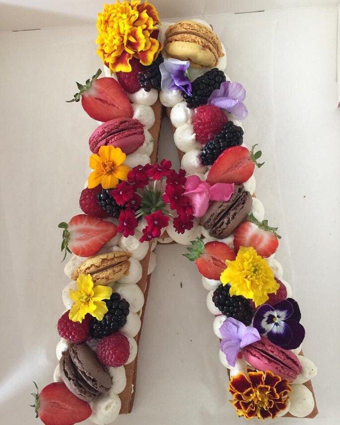 Com'Lo, gâteau de mariage en form de A avec des macarons, des fruits rouge et des fleurs jaune comestibles